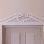 Decorazione di porta con cornice e pannelli a trompe l'oeil